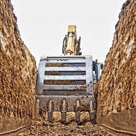 picture of excavator  - Excavator digging a deep trench on the site focus forward - JPG
