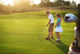 picture of golf bag  - Casual kids at a golf field holding golf clubs - JPG
