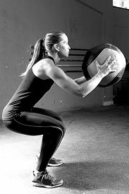 foto of slam  - profile of a young female athlete crouched doing wall balls exercises at the gym  - JPG