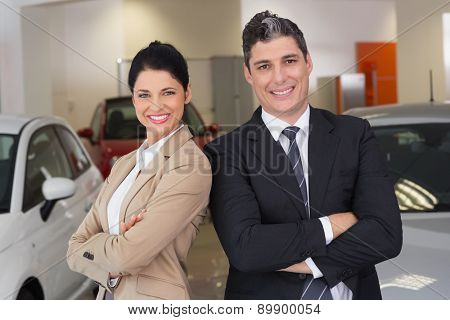 Business team standing with arms crossed at new car showroom