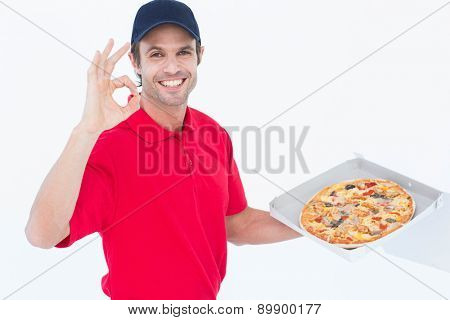 Portrait of happy delivery man gesturing okay while holding fresh pizza on white background