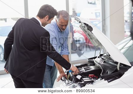 Two men looking at a car engine at new car showroom
