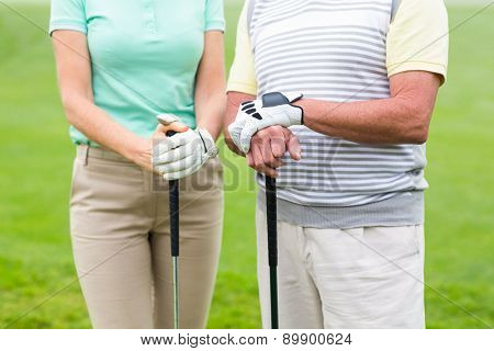 Golfing couple holding clubs on a foggy day at the golf course