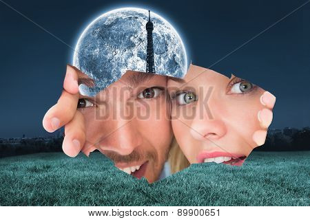 Young couple peeking through torn paper against large moon over paris