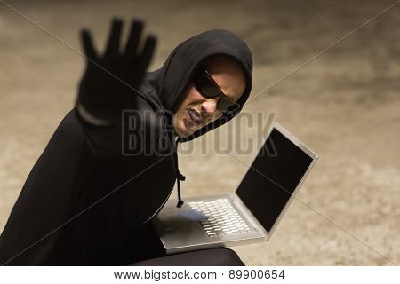 Frowning hacker in sunglasses gesturing on white background