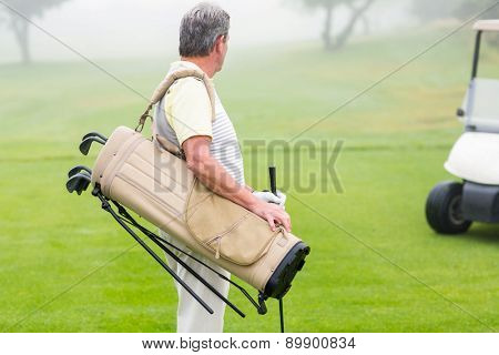 Happy golfer with golf buggy behind on a foggy day at the golf course
