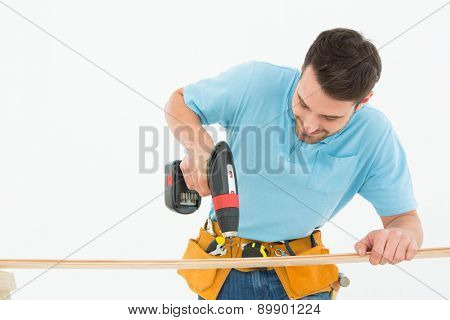 Male construction worker using hand drill on wooden plank against white background