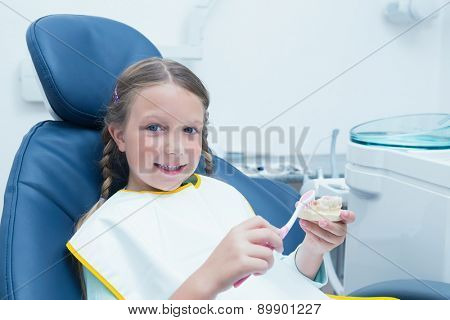 Little girl learning how to brush teeth in the dentists chair