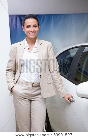 Smiling businesswoman holding a car door handles at new car showroom