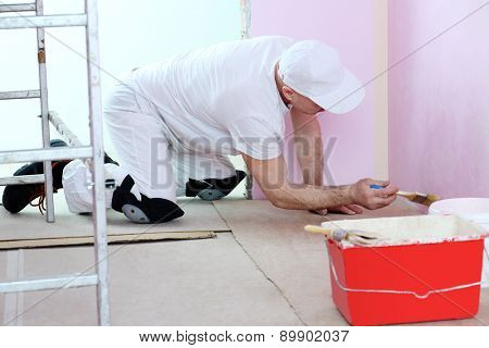 Finisher in white clothes with a brush in hand painted walls in pink room near the floor