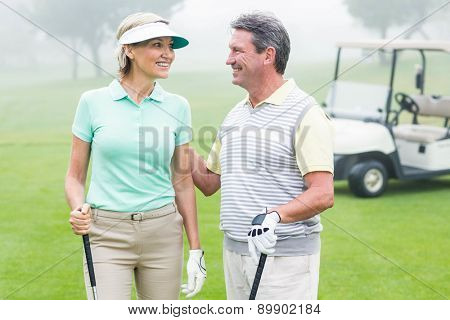 Happy golfing couple facing each other with golf buggy behind on a foggy day at the golf course