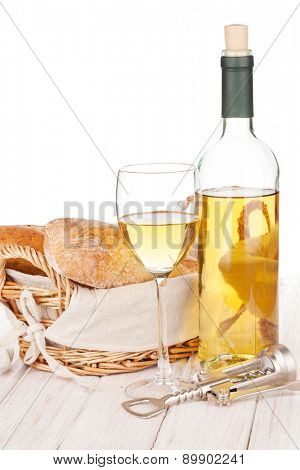 White wine and bread on white wooden table