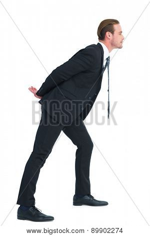 Businessman in suit leaning over on white background