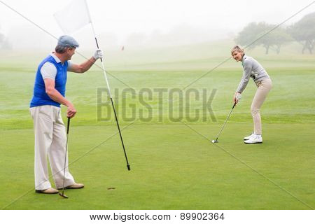 Golfing couple on the golf course on a foggy day
