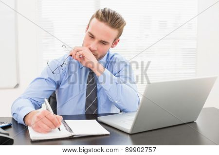 Businessman holding glasses and taking notes in his office