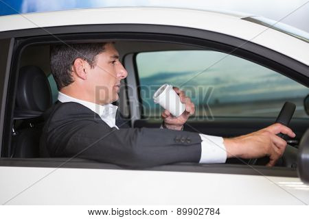 Serious businessman drinking coffee while driving in his car