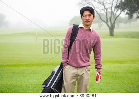 Golfer standing holding his golf bag at the golf course