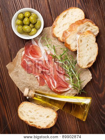 Bruschetta ingredients - prosciutto, olives and olive oil. Top view on wooden table