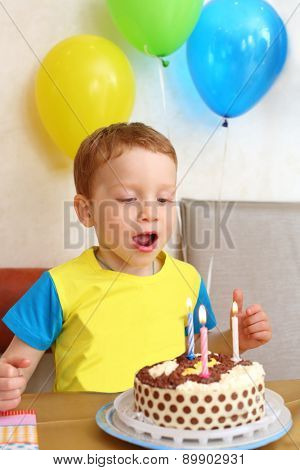 Little boy blows out the candles on the birthday cake in cafe