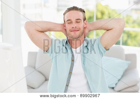 Cheerful businessman resting with hands behind head in his offce