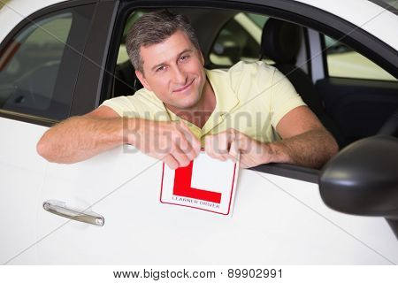 Cheerful male driver tearing up his L sign at new car showroom