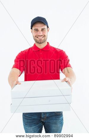 Portrait of happy delivery man giving pizza boxes on white background