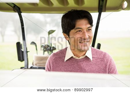 Happy golfer driving his golf buggy at the golf course