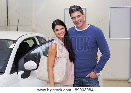 Smiling couple standing in front of a car at new car showroom