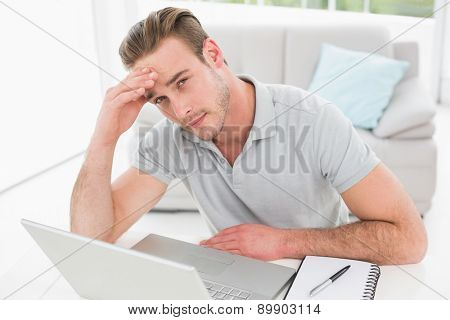 Anxious businessman using laptop and notebook in his office