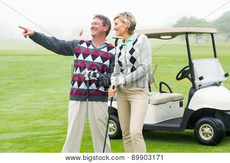Happy golfing couple with golf buggy behind on a foggy day at the golf course