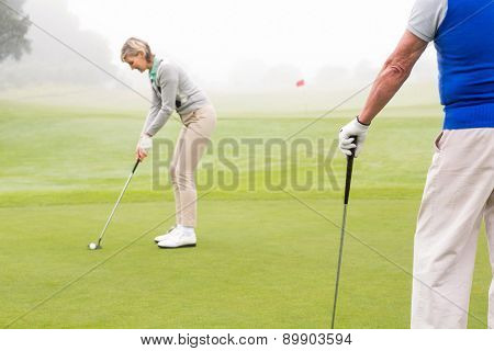 Lady golfer teeing off for the day watched by partner on a foggy day at the golf course