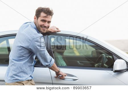Young man opening the door of his car