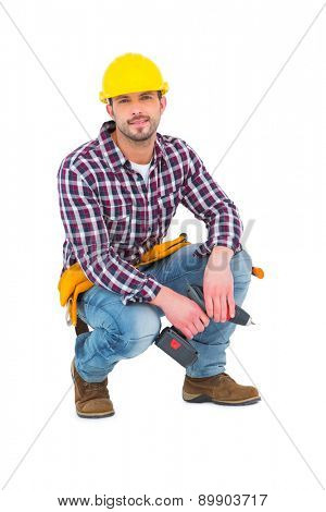 Crouching handyman holding power drill on white background