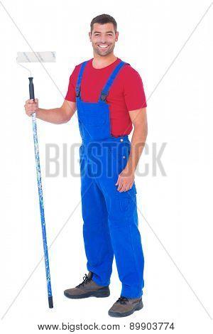 Full length portrait of handyman in overalls holding paint roller on white background