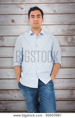 Unsmiling casual man standing against wooden planks