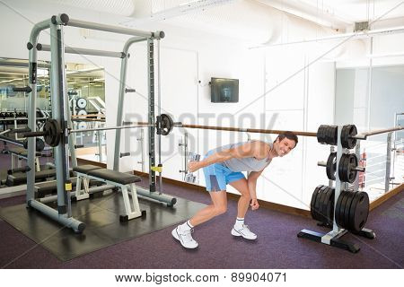 Smiling fit young man exercising with dumbbell against empty weights room with bench press