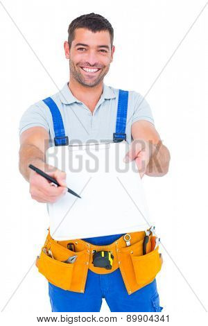 Portrait of smiling handyman giving clipboard for signature on white background