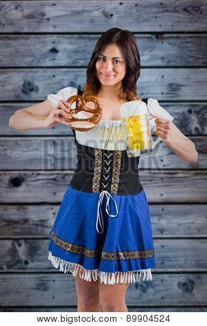 Pretty oktoberfest girl holding beer tankard and pretzel against wooden background in blue