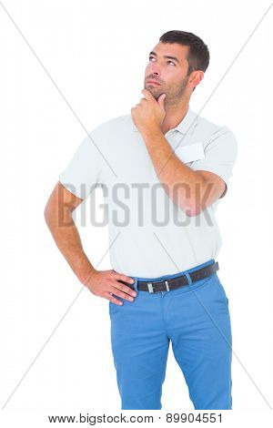 Thoughtful male technician with hand on chin looking up over white background