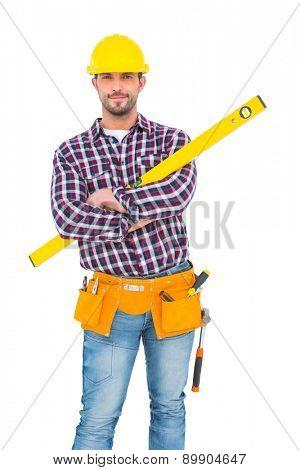 Smiling handyman holding spirit level on white background