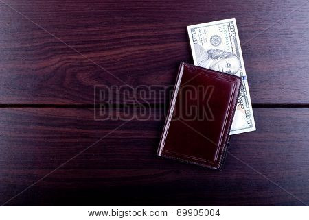 Maroon Purse With Hundred Dollar Bills On A Burgundy Table, Top View
