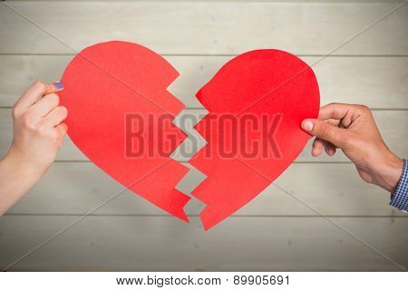 Two hands holding broken heart against bleached wooden planks background