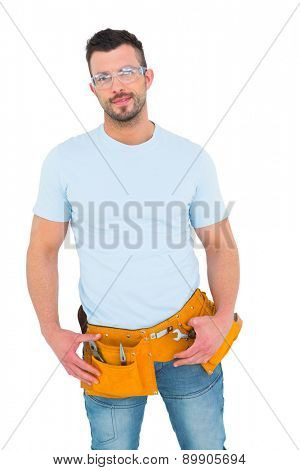 Smiling handyman with hands on hips on white background