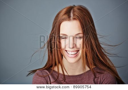 Ecstatic girl with dark long hair and toothy smile