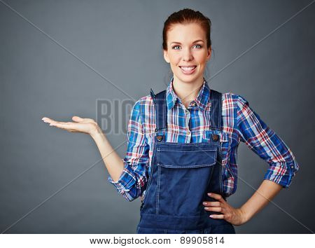 Happy young woman in coveralls keeping her palm open