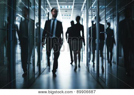 Busy employees going down office building corridor