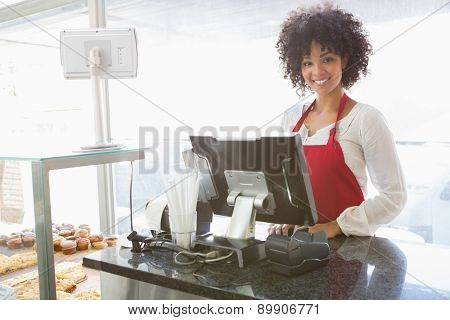 Beautiful waitress posing behind the counter at the bakery