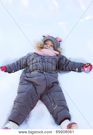 Child Lying On The Snow And Playing In Winter Day