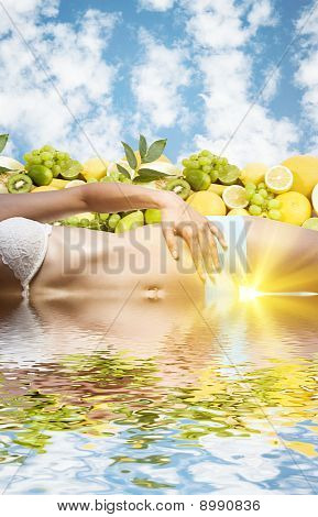 Beautiful female body in water over fruits and sky