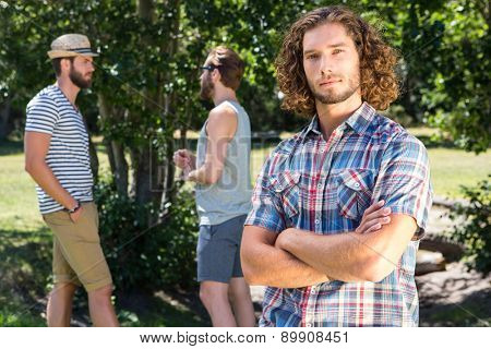 Young man frowning at camera in the park on a summers day